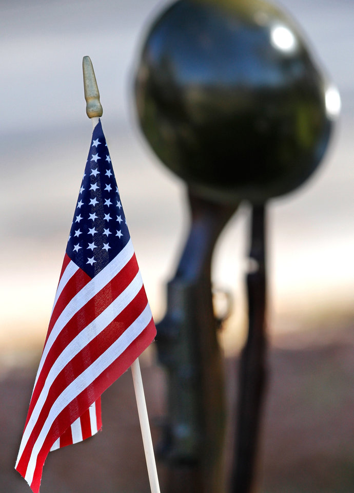 Photo - A small American flag is placed in the ground next to a sculpture of a soldier's helmet resting atop a rifle at  a ceremony Wednesday, Dec. 7, 2011, near NW 13 and Broadway in Oklahoma City,  to commemorate the 70th anniversary of the Japanese attack on US forces at Pearl Harbor in 1941. The memorial was held  in front of the anchor salvaged  from the USS Oklahoma after it sank.    Photo by Jim Beckel, The Oklahoman