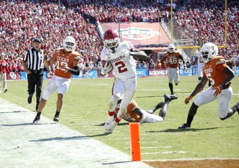 Photo -  OU's CeeDee Lamb tight-rope walks the sideline on his way to a touchdown during the second half of Saturday's game vs. Texas in Dallas. Lamb set a career high with 10 receptions in the Sooners' 34-27 victory. [Sarah Phipps/The Oklahoman]