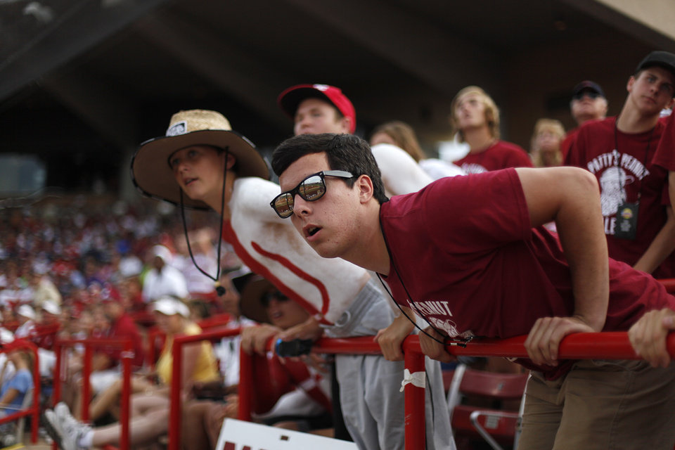 Photo - Adam Mitchell and Brice Turang watch in anticipation during a Women's College World Series softball game between OU and Alabama at ASA Hall of Fame Stadium in Oklahoma City, Tuesday, June 5, 2012.  Photo by Garett Fisbeck, The Oklahoman