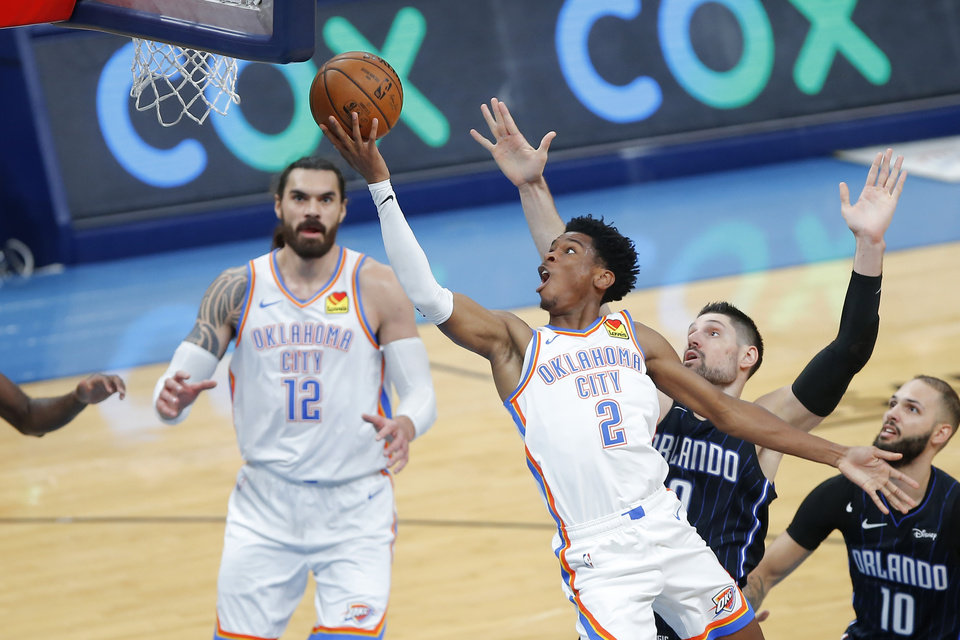 Photo - Oklahoma City's Shai Gilgeous-Alexander (2) goes past Orlando's Nikola Vucevic (9) to the basket during an NBA basketball game between the Oklahoma City Thunder and the Orlando Magic at Chesapeake Energy Arena in Oklahoma City, Tuesday, Nov. 5, 2019. Oklahoma City won 102-94. [Bryan Terry/The Oklahoman]