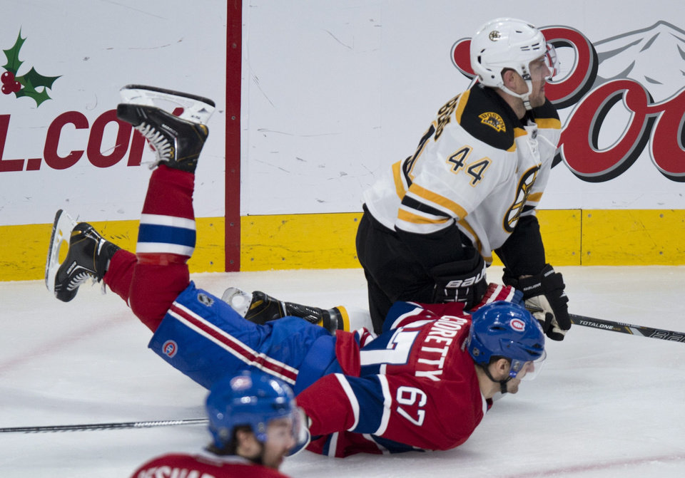 Photo - Montreal Canadiens' Max Pacioretty is dumped by Boston Bruins' Dennis Seidenberg during first period NHL hockey action Thursday, Dec. 5, 2013, in Montreal. (AP Photo/The Canadian Press, Paul Chiasson)
