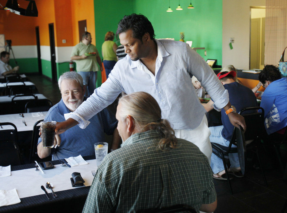 Owner William Bathini attends to customers at Heritage India. <strong>PAUL HELLSTERN - Oklahoman</strong>