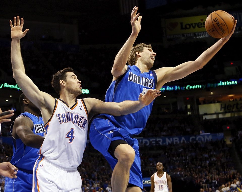 Dallas' Dirk Nowitzki (41) grabs a rebound next to Oklahoma City's Nick Collison (4) during an NBA basketball game between the Oklahoma City Thunder and the Dallas Mavericks at Chesapeake Energy Arena in Oklahoma City, Sunday, March 16, 2014. Photo by Nate Billings, The Oklahoman