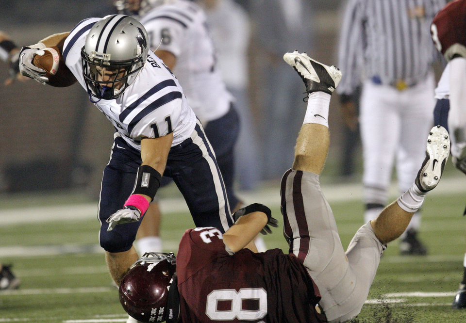 Photo - Edmond North's Jared Benway is brought down by Edmond Memorial's Chase Thackerson during the high school football game between Edmond North and Edmond Memorial at Wantland Stadium in Edmond, Okla., Friday, Sept. 16, 2011. Photo by Sarah Phipps, The Oklahoman