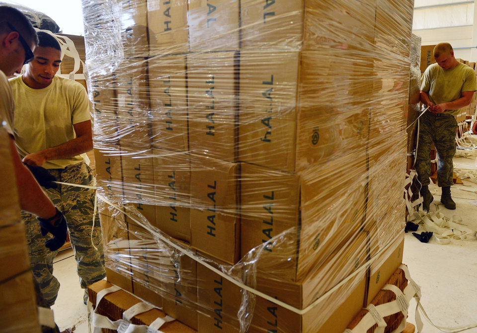 Photo - This Aug. 7, 2014, image released by the U.S. Air Force shows U.S. Airmen with the 8th Expeditionary Air Mobility Squadron palletize halal meals for a humanitarian airdrop in Iraq on Thursday, Aug. 7, 2014, at an undisclosed location in Southwest Asia. (AP Photo/U.S. Air Force, Staff Sgt. Vernon Young Jr.)