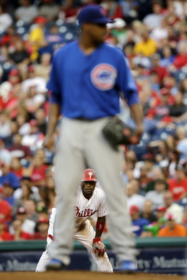 Photo - Philadelphia Phillies' Jimmy Rollins, bottom, takes a lead off first base as Chicago Cubs' Edwin Jackson stands on the mound in the first inning of a baseball game, Tuesday, Aug. 6, 2013, in Philadelphia. (AP Photo/Matt Slocum)