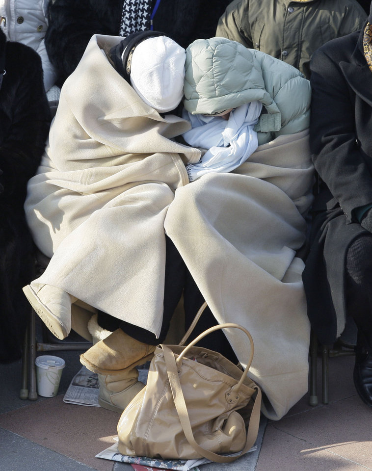 Photo - Two unidentified attendees stay warm as they wait for the inauguration of Barack Obama and Joe Biden at the U.S. Capitol in Washington, Tuesday, Jan. 20, 2009.  (AP Photo/Elise Amendola)
