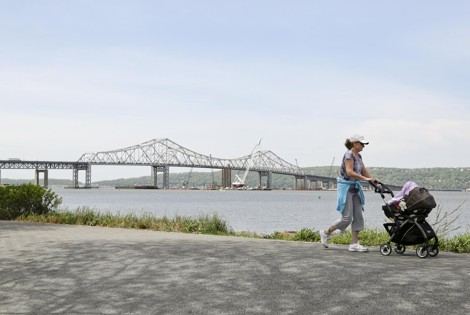 Photo - A woman takes a stroll with her child along the Westchester Riverwalk just north of the Tappan Zee Bridge, Tuesday, May 13, 2014, in Tarrytown, N.Y. On Wednesday, President Barack Obama plans to speak by the bridge just north of New York City to press his case that a key federal government fund used to pay for the nation's roads, bridges and ports is running dry and that the economy would be damaged if it is not replenished. (AP Photo/Julie Jacobson)