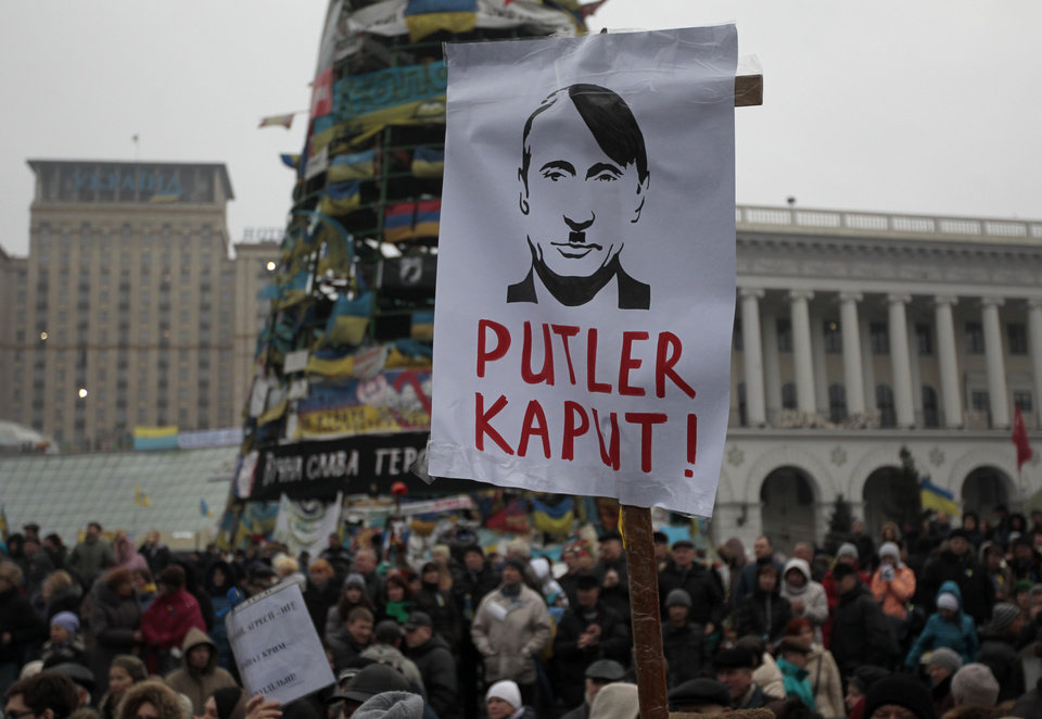 Photo - A poster with the caricature of Russian President Vladimir Putin,  on display as people gather during a rally in Kiev's Independence Square, Sunday, March 2, 2014. Ukraine's new prime minister urged Russian President Vladimir Putin to pull back his military Sunday in the conflict between the two countries, warning that