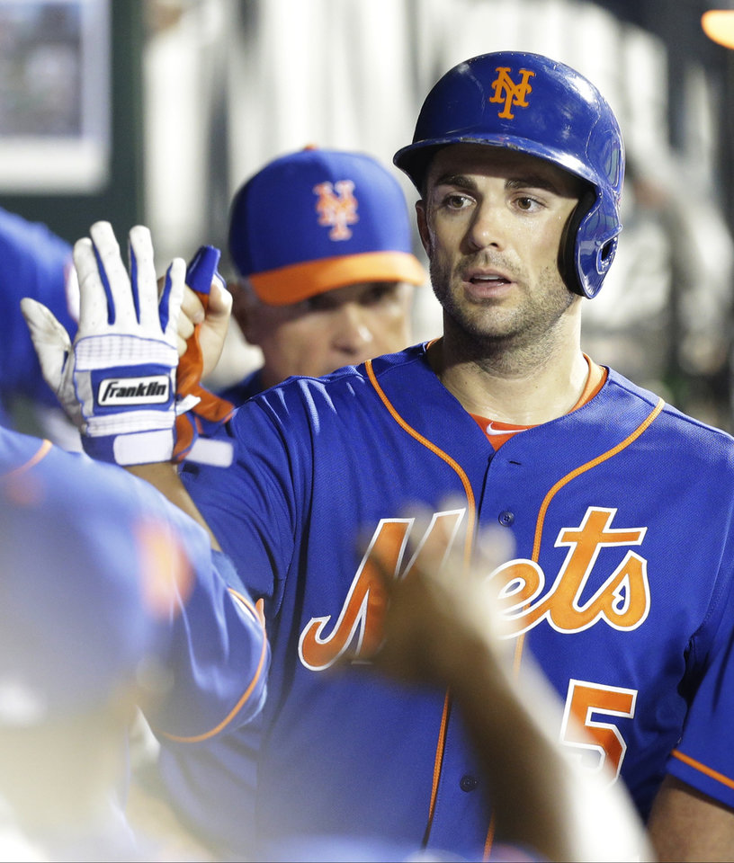 Photo - New York Mets' David Wright celebrates with teammates after scoring on a walk during the sixth inning of a baseball game against the Chicago Cubs, Saturday, Aug. 16, 2014, in New York. (AP Photo/Frank Franklin II)