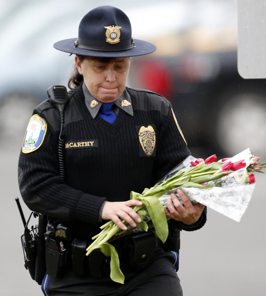 Photo - Newtown Police Officer Maryhelen McCarthy places flowers at a makeshift memorial outside St. Rose of Lima Roman Catholic Church, Sunday, Dec. 16, 2012, in Newtown, Conn. On Friday, a gunman allegedly killed his mother at their home and then opened fire inside the Sandy Hook Elementary School, killing 26 people, including 20 children. (AP Photo/Julio Cortez)