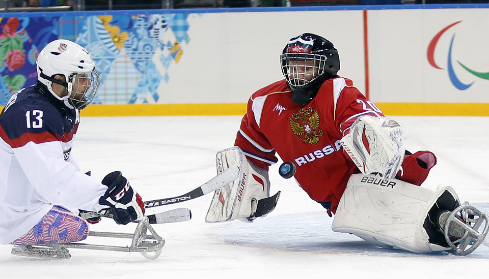 Photo - United States's Joshua Sweeney, left, shots on goal as Russia's Vladimir Kamantcev, right, try to defend during the gold medal ice sledge hockey match between United States and Russia at the 2014 Winter Paralympics in Sochi, Russia, Saturday, March 15, 2014. (AP Photo/Pavel Golovkin)
