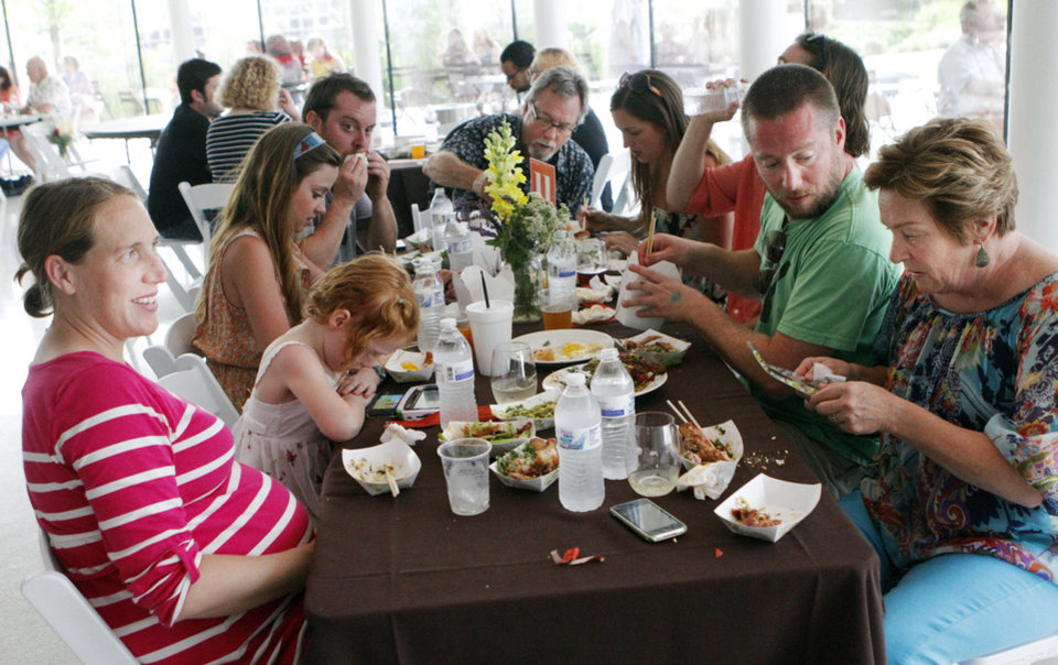 Photo - The Gautreaux family from Oklahoma City eats Chinese cuisine at the OK Chefs Relief in the Myriad Gardens of Oklahoma City on May 27, 2013. Photo by KT King, The Oklahoman