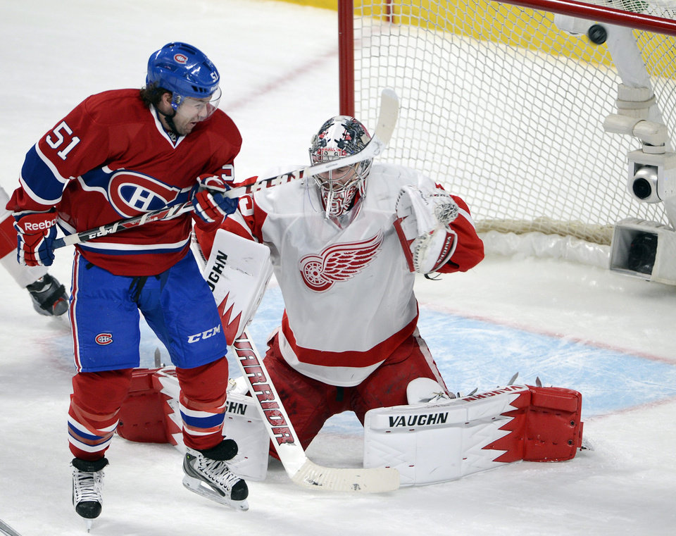Photo - Montreal Canadiens center David Desharnais (51) is stopped by Detroit Red Wings goalie Jimmy Howard (35) during the second period of an NHL hockey game Wednesday, Feb. 26, 2014, in Montreal. (AP Photo/The Canadian Press, Ryan Remiorz)