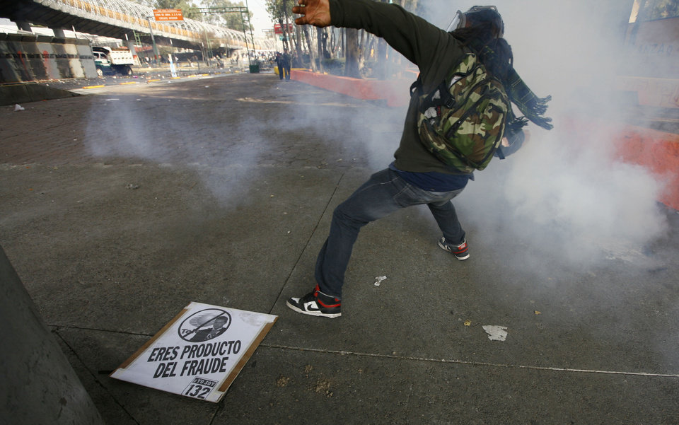 Photo - A demonstrator throws a stone to police during protests against new Mexican President Enrique Pena Nieto's rule, outside the National Congress, in Mexico City, Saturday, Dec. 1, 2012.   Pena Nieto took the oath of office as Mexico's new president on Saturday amid protests inside and outside the congressional chamber where he swore to protect the constitution and laws of the land. At least two protesters were injured, one gravely. The sign on the floor reads in Spanish