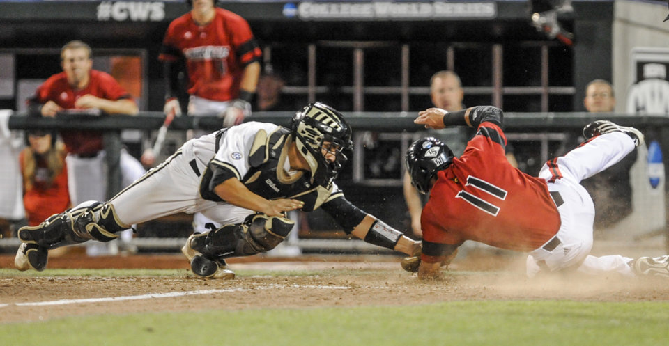 Photo - Louisville's Zach Lucas, right, slides home past Vanderbilt catcher Karl Ellison on a single by Nick Solak in the seventh inning of an NCAA baseball College World Series game in Omaha, Neb., Saturday, June 14, 2014. (AP Photo/Dave Weaver)