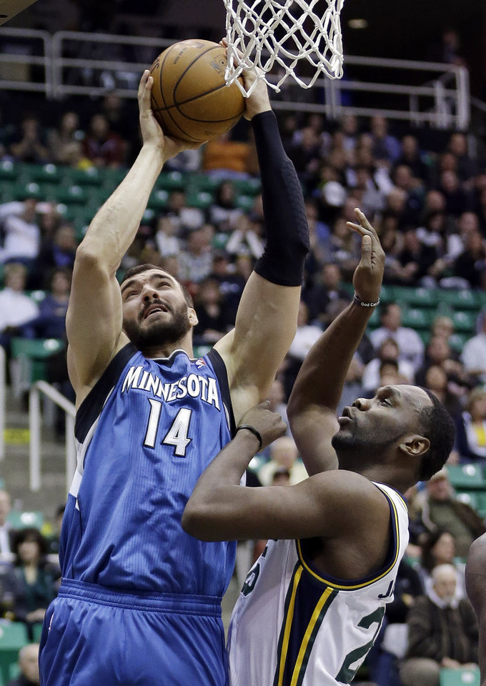 Minnesota Timberwolves center Nikola Pekovic (14) goes to the basket as Utah Jazz center Al Jefferson (25) defends in the first quarter during an NBA basketball game on Wednesday, Jan. 2, 2013, in Salt Lake City. (AP Photo/Rick Bowmer)