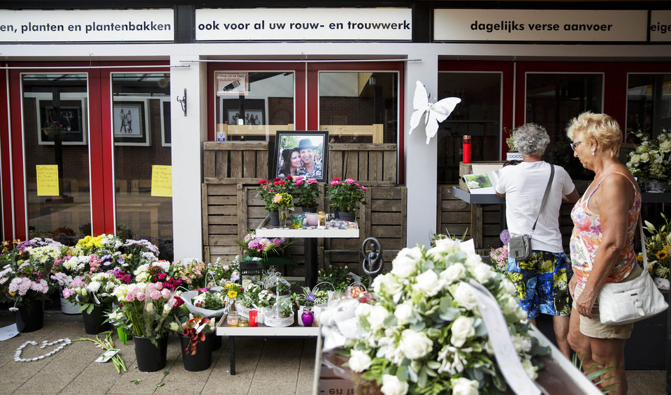 Photo - Women stand near to a portrait of Neeltje Tol, left, and Cor Schilder, right, placed with flowers and candles in front of their flower shop in Volendam, Netherlands, Saturday, July 19, 2014. An attack on a Malaysian jetliner shot down over Ukraine on Thursday killed 298 people from nearly a dozen nations, more than half being Dutch. Tol and Schilder were among those killed. (AP Photo/Phil Nijhuis)