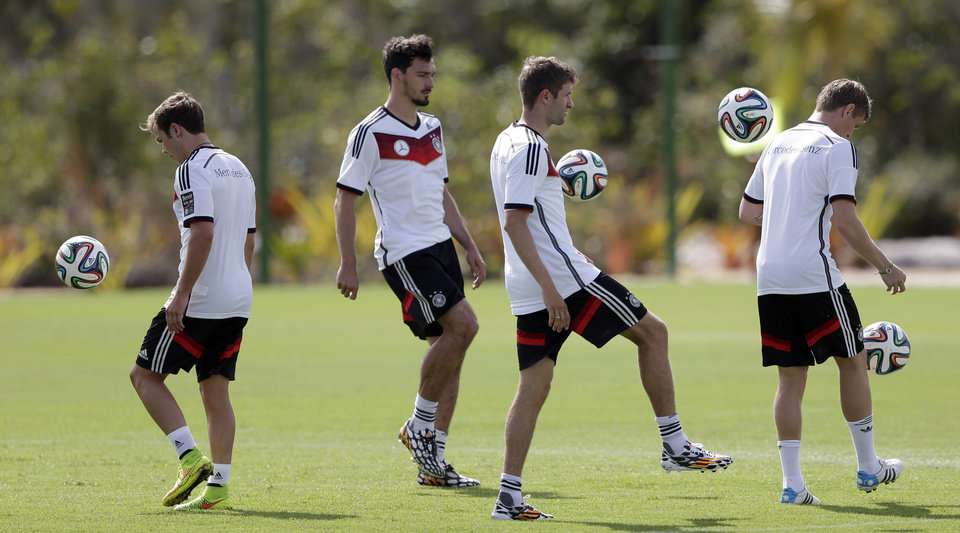 Photo - German national soccer players Mario Goetze, from left, Mats Hummels, Thomas Mueller and Toni Kross joggle balls during a training session in Santo Andre near Porto Seguro, Brazil, Thursday, June 12, 2014. Germany will play in group G of the 2014 soccer World Cup. (AP Photo/Matthias Schrader)