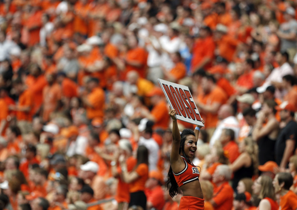 Photo - A Oklahoma State cheerleader encourages fans to cheer during first half of the AdvoCare Texas Kickoff college football game between the Oklahoma State University Cowboys (OSU) and the Mississippi State University Bulldogs (MSU) at Reliant Stadium in Houston, Saturday, Aug. 31, 2013. Photo by Sarah Phipps, The Oklahoman