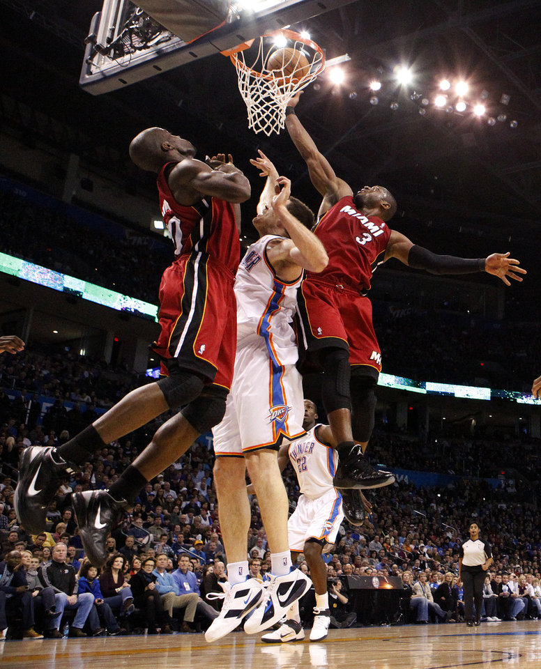 Photo - Miami's Dwyane Wade (3) shoots over Oklahoma City's Nick Collison (4) as Miami's Joel Anthony (50) positions for a rebound during the NBA basketball game between Oklahoma City and Miami at the OKC Arena in Oklahoma City, Thursday, Jan. 30, 2011. Photo by Sarah Phipps, The Oklahoman