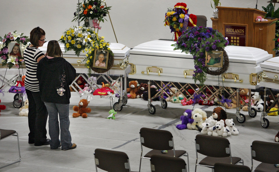 Mourners gather by the caskets of Summer Rust and her four children Kirsten Rust, Autumn Rust, Teagin Rust and Evynn Garas before funeral services at Redlands Community College in El Reno, Okla. on Wednesday, Jan. 21, 2009. Rust and her children were killed earlier this month in their apartment in El Reno, Okla. 