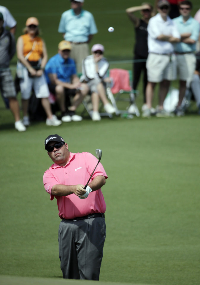 Photo - Kevin Stadler chips to the second green during the second round of the Masters golf tournament Friday, April 11, 2014, in Augusta, Ga. (AP Photo/Chris Carlson)