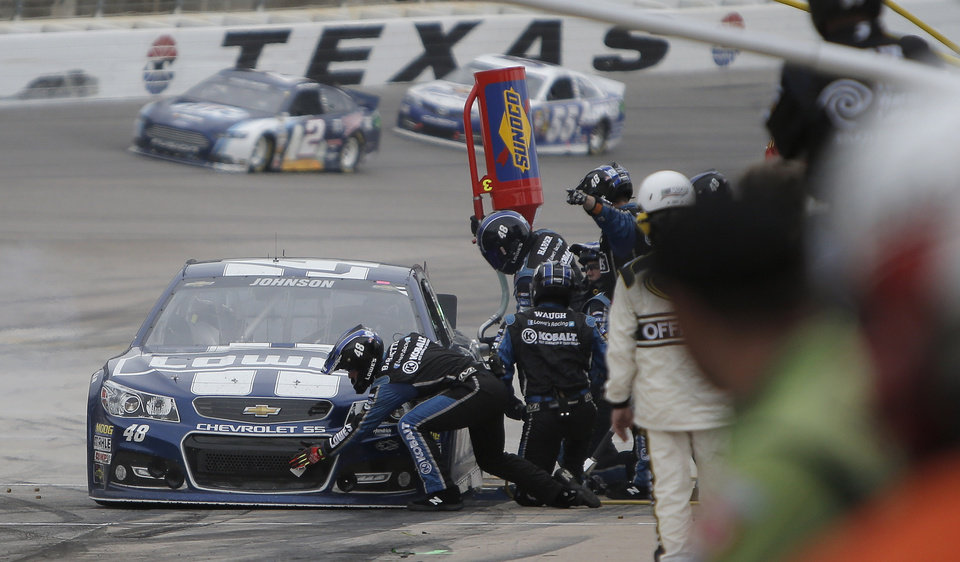 Photo - The pit crew for Jimmie Johnson work on his car during the NASCAR Sprint Cup series auto race at Texas Motor Speedway in Fort Worth, Texas, Sunday, Nov. 3, 2013. (AP Photo/Brandon Wade)