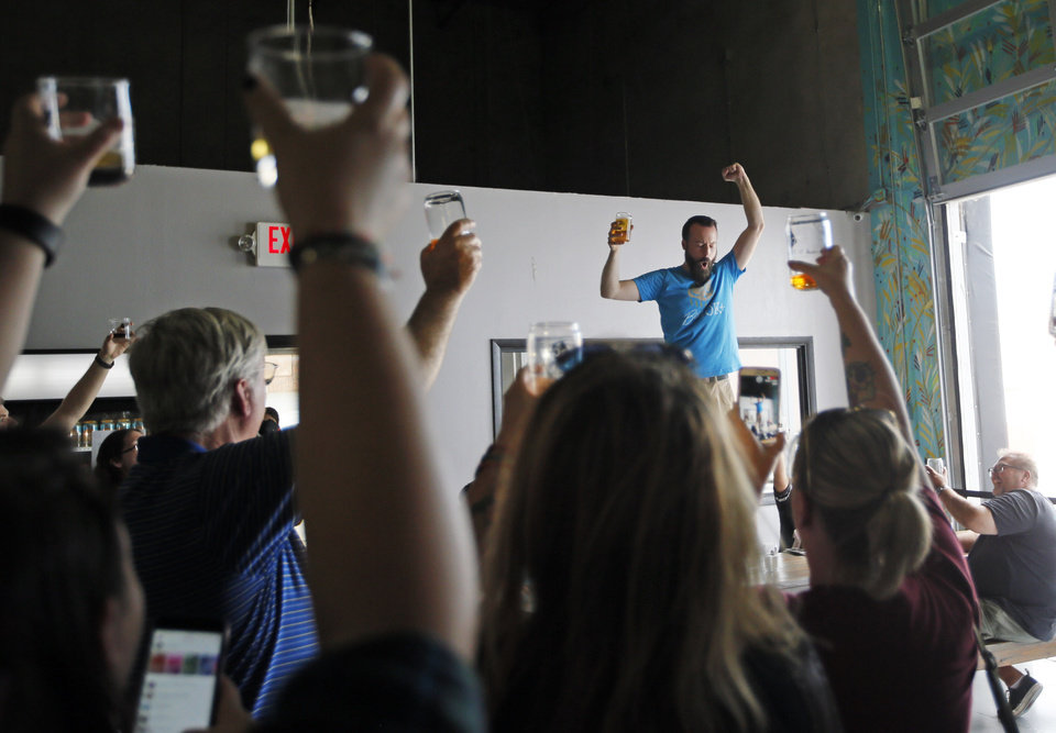 Photo - Tap room manager Ben Childers leads people in raising a glass to Senate Bill 424 at 4:24 pm at Anthem Brewing Company, 908 SW 4th St., in Oklahoma City, Friday, Aug. 26, 2016. Senate Bill 424 went into effect on Friday, allowing people to purchase and consume full-strength beer on premises at Oklahoma breweries for the first time since statehood. Photo by Nate Billings, The Oklahoman