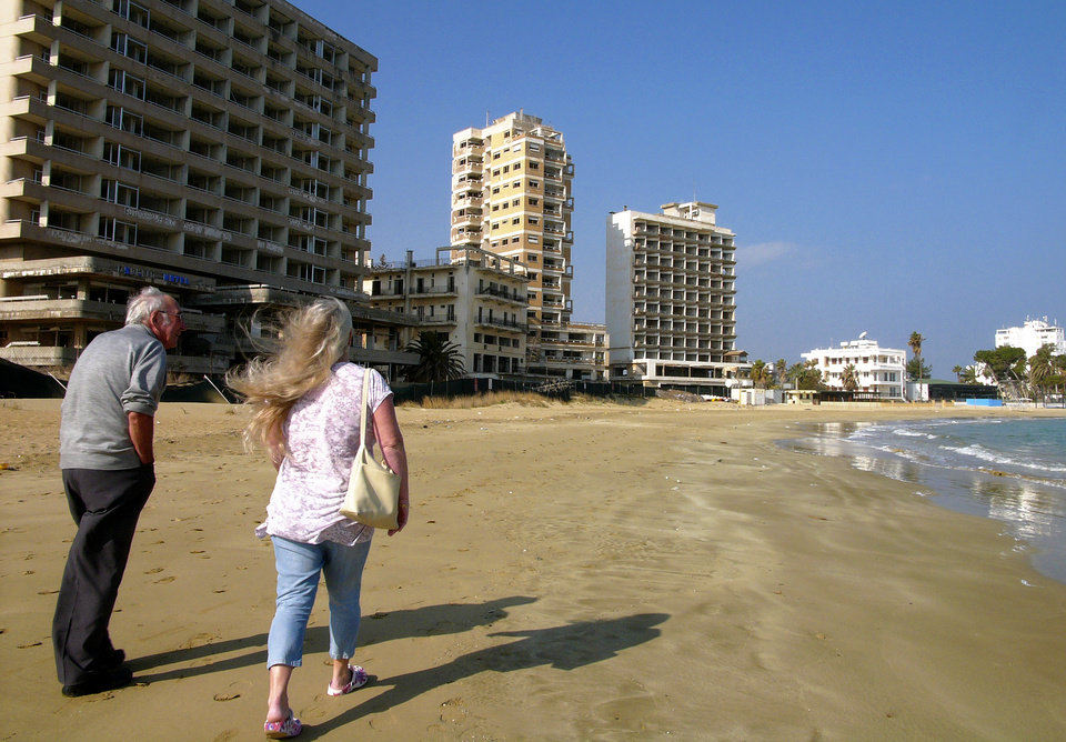 Photo - A couple walk on the beach by the deserted hotels in an area used by the Turkish military in the Turkish occupied area in abandoned coastal city of Varosha, in Famagusta, in southeast of island of Cyprus, Friday, Jan. 17, 2014. Time virtually stopped in 1974 for the Mediterranean tourist playground of Varosha. When Turkey invaded Cyprus in the wake of a coup by supporters of union with Greece, thousands of residents fled, and chain-link fences enclosed a glamorous resort that it's said once played host to Hollywood royalty like Elizabeth Taylor. The town's crumbling, war-scarred beachfront hotels have become an emblem of the country's division between Turks and Greeks. In 40 years, few have set foot inside the town, which remains heavily guarded by the Turkish army and twists of barbed wire. But that grim scene could present a rare opportunity. Massachusetts Institute of Technology architecture professor Jan Wampler calls it the greatest challenge of his career: he and a team of architects, urban planners, business leaders and peace activists hope to rebuild an entire town to correct past errors and mold a sustainable, ecological habitat.  (AP Photo/Petros Karadjias)
