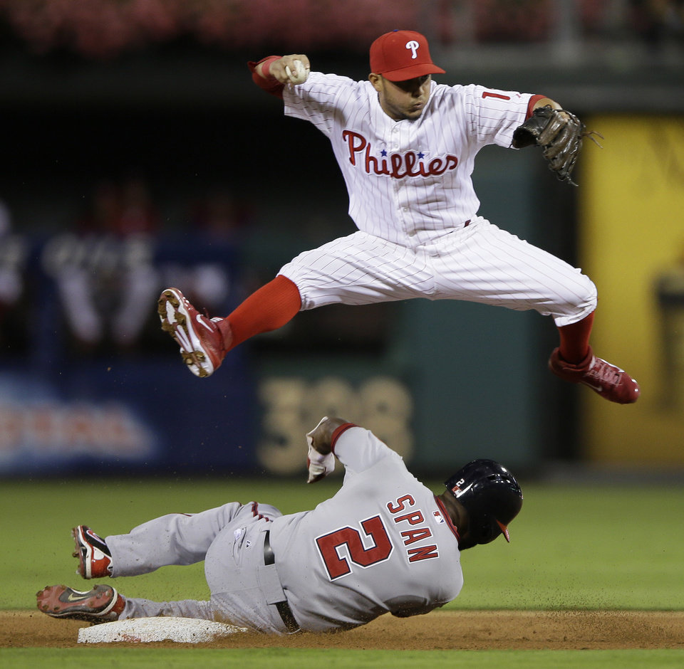 Photo - Philadelphia Phillies shortstop Freddy Galvis, top, leaps over Washington Nationals' Denard Span after forcing him out at second base on a ball hit by Bryce Harper, who was safe at first during the third inning of a baseball game, Tuesday, Sept. 3, 2013, in Philadelphia. (AP Photo/Matt Slocum)
