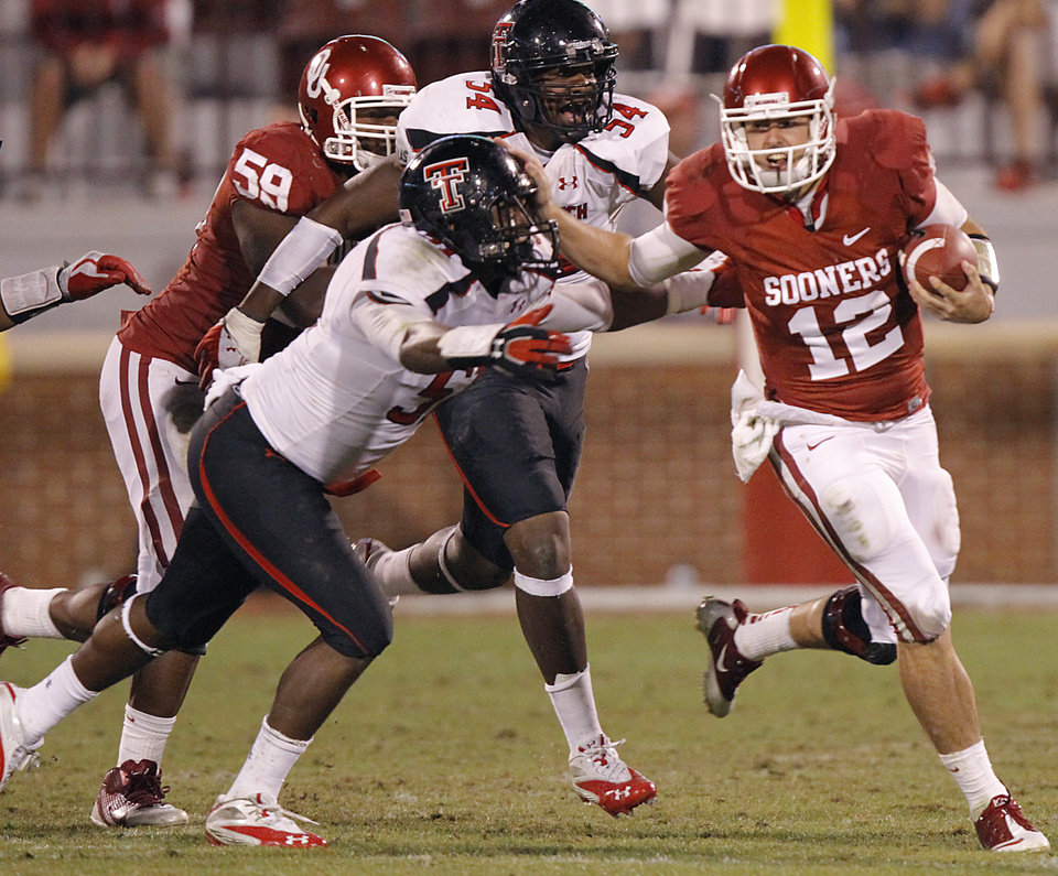 Oklahoma's Landry Jones (12) tries to get away from Texas Tech's Cqulin Hubert (51) and Sawyer Vest (34) during the college football game between the University of Oklahoma Sooners (OU) and Texas Tech University Red Raiders (TTU) at the Gaylord Family-Oklahoma Memorial Stadium on Sunday, Oct. 23, 2011. in Norman, Okla. Photo by Chris Landsberger, The Oklahoman