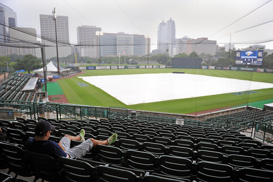 Photo - Usher Cody Moles waits out a rain delay before an NCAA college baseball tournament regional game between George Mason and Texas A&M, Saturday, May 31, 2014, at Reckling Park in Houston. (AP Photo/Houston Chronicle, Eric Christian Smith) MANDATORY CREDIT