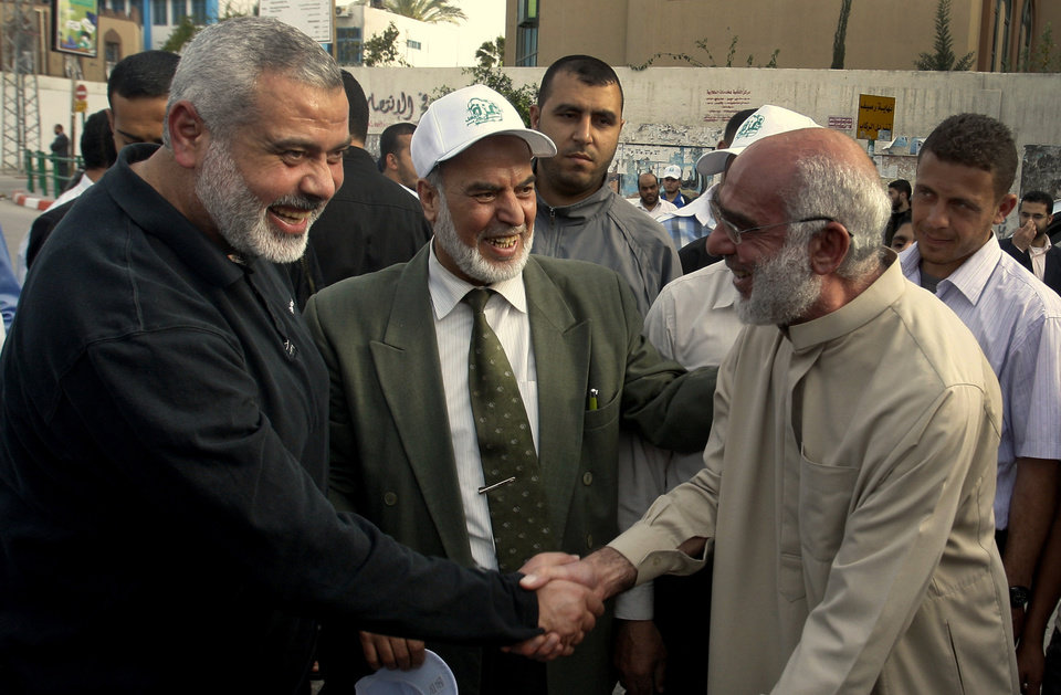 Photo - Gaza's Hamas Prime Minister Ismail Haniyeh, left, takes part in a tree planting ceremony during May Day celebrations in Gaza City, Monday, May 2, 2011. Haniyeh condemned the United States on Monday for killing al-Qaida chief Osama bin Laden, saying the operation marked