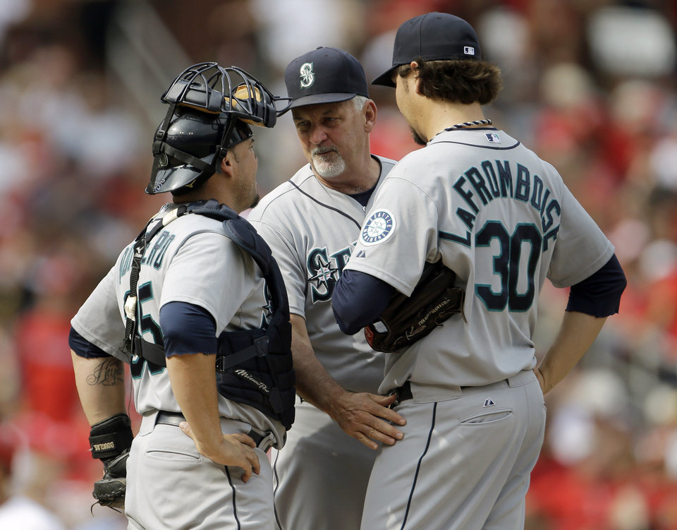 Photo - Seattle Mariners pitching coach Carl Willis, center, talks with catcher Humberto Quintero, left, and relief pitcher Bobby LaFromboise during the fifth inning of a baseball game against the St. Louis Cardinals Sunday, Sept. 15, 2013, in St. Louis. (AP Photo/Jeff Roberson)