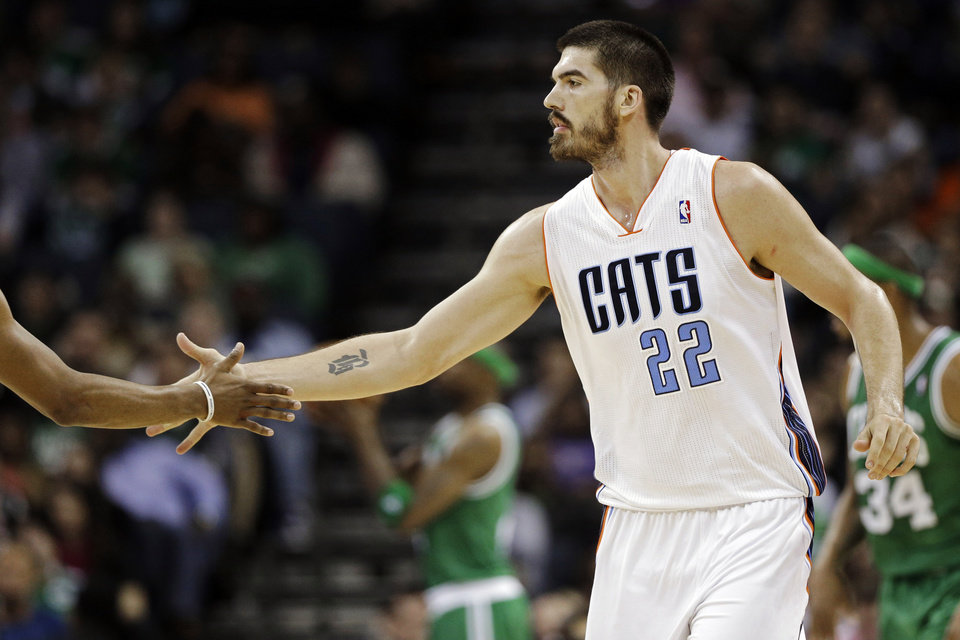 Photo - Charlotte Bobcats' Byron Mullens (22) is congratulated by a teammate after making a basket against the Boston Celtics during the second half of an NBA basketball game in Charlotte, N.C., Monday, Feb. 11, 2013. The Bobcats won 94-91. (AP Photo/Chuck Burton)