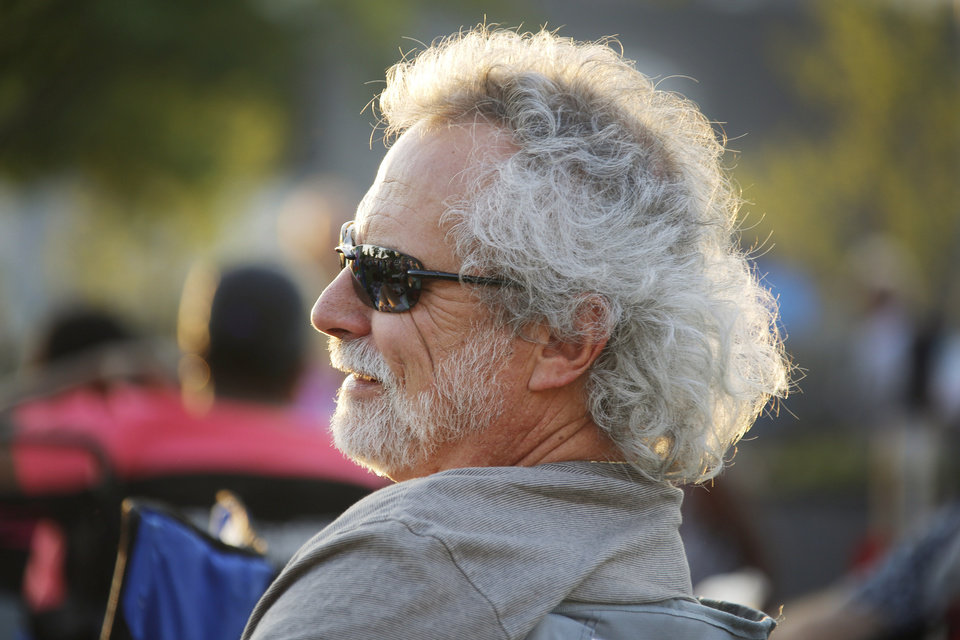 Photo -  Glenn Blumsteim relaxes while listening to Zoom City perform during a free concert presented by Allied Arts. Photo by Doug Hoke, The Oklahoman   DOUG HOKE -
