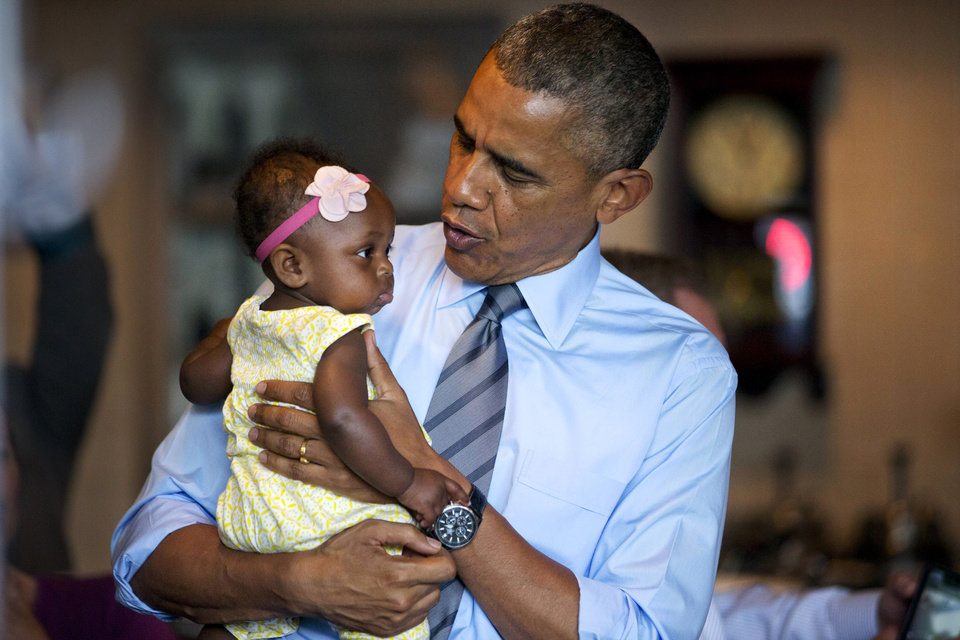 Photo - President Barack Obama holds seven-month-old Jaidyn Oates during a stop at the Charcoal Pit in Wilmington, Del., Thursday, July 17, 2014, en route to speak about transportation and infrastructure. (AP Photo/Jacquelyn Martin)