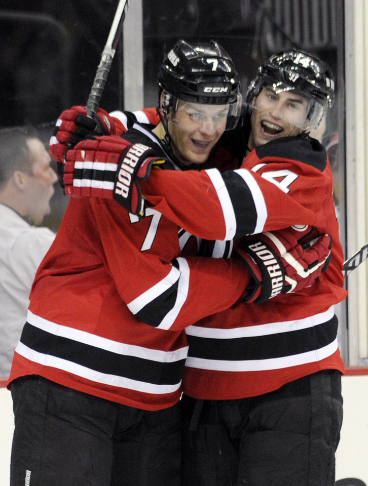 Photo - New Jersey Devils' Mark Fayne, left, celebrates with Adam Henrique after Fayne scored during the second period of an NHL hockey game Thursday, March 20, 2014, in Newark, N.J. (AP Photo/Bill Kostroun)