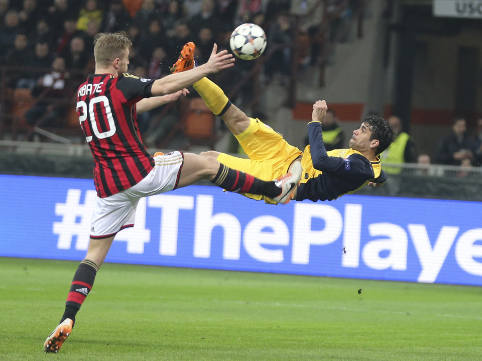 Photo - Atletico Madrid Brazilian forward Diego Costa tries an acrobatic shot as AC Milan defender Ignazio Abate tries to stop him during a Champions League, round of 16, first leg, soccer match between AC Milan and Atletico Madrid at the San Siro stadium in Milan, Italy, Wednesday, Feb. 19, 2014. (AP Photo/Antonio Calanni)