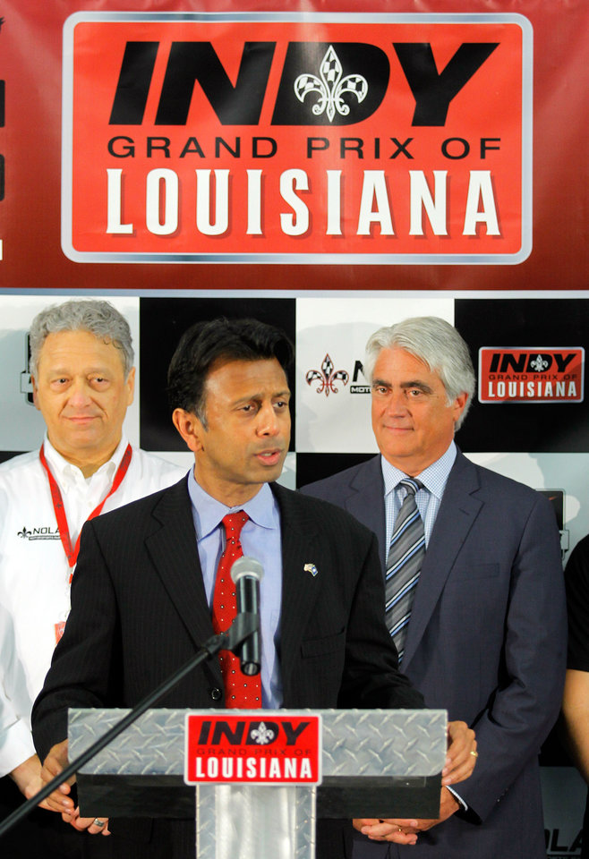 Photo - NOLA Motorsports owner Laney Chouest, left and Mark Miles, CEO of IndyCar, right, listen as Louisiana Governor Bobby Jindal announces during a press conference Monday, May 5, 2014,  that IndyCar will race at NOLA Motorsports Park in Avondale next year. (AP Photo/ NOLA.com The Times-Picayune David Grunfeld)