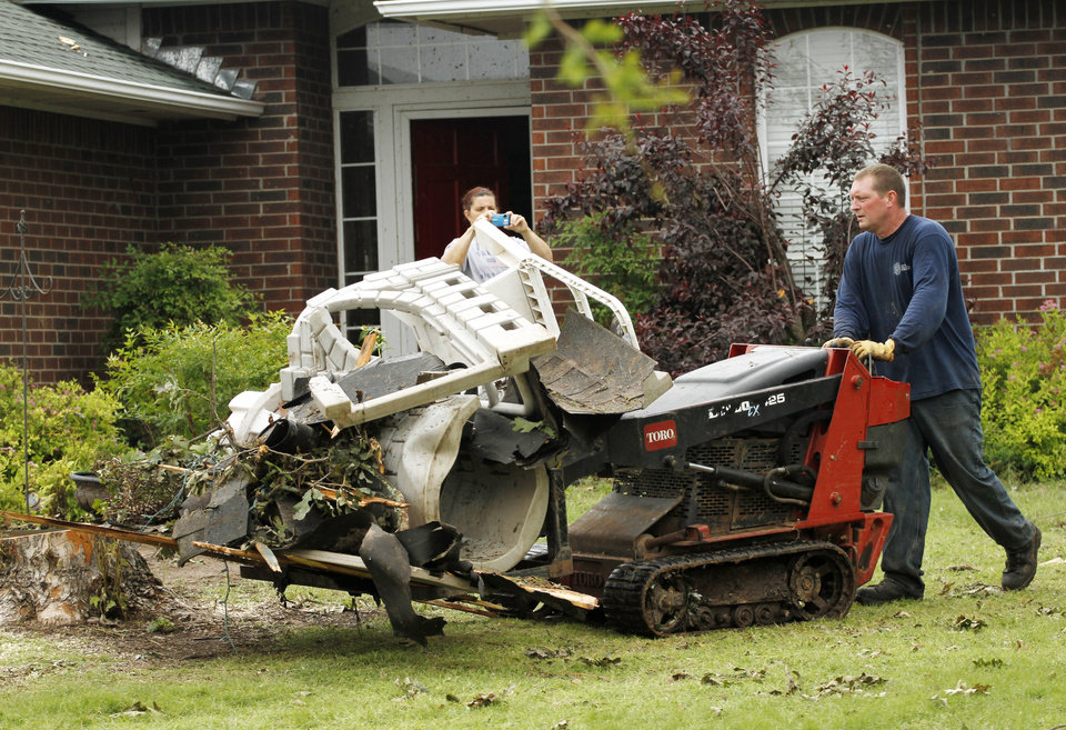 Homeowner Mike Paschal takes debris to the street in the Dripping Springs Estates Saturday, May 15, 2010. Saturday hundreds of volunteers went into areas that had been affected by last week's tornadoes to help clear debris. Photo by Doug Hoke, The Oklahoman.