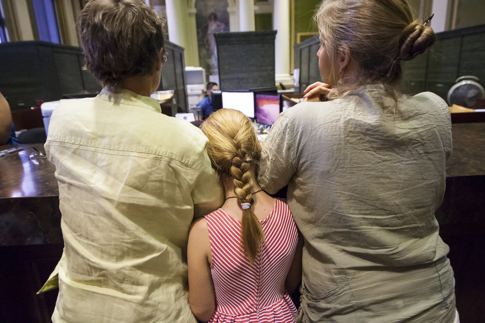 Photo - Deborah Crippen, left, and Lynn Menefee fill out their marriage license application while their daughter, Emma Crippen-Menefee, squeezes between them at the Pueblo County Courthouse in Pueblo, Colo., Friday, July 11, 2014. Technically, their state still does not recognize gay marriages. But that hasn't stopped hundreds of gay Coloradans from getting marriage licenses from two county clerks who argue they still have the legal right to provide them to loving couples. (AP Photo/The Colorado Springs Gazette, Julia Moss)
