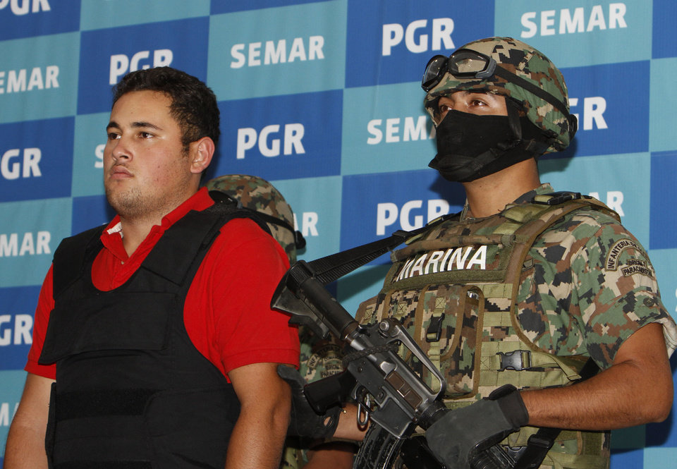 Photo -   A Mexican marine escorts Jesus Alfredo Guzman Salazar, left, during his presentation to the media in Mexico City, Thursday, June 21, 2012. Mexican marines detained Jesus Alfredo Guzman Salazar, 26, one of the sons of Mexico's most-wanted drug kingpin, Joaquin