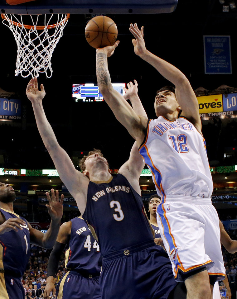 Photo - Oklahoma City's Steven Adams (12) shoots beside New Orleans' Omer Asik (3) during an NBA game between the Oklahoma City Thunder and the New Orleans Pelicans at Chesapeake Energy Arena on Friday, Feb. 6, 2015. Photo by Bryan Terry, The Oklahoman
