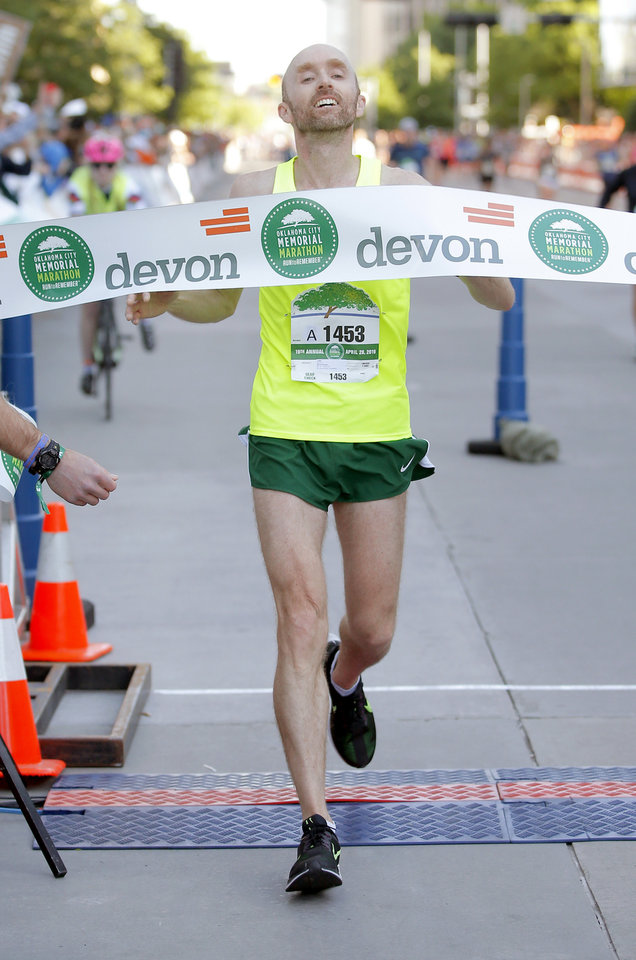 Photo - David Rhodes crosses the finish line to win the men's Oklahoma City Memorial Marathon in Oklahoma City, Sunday, April 28, 2019. [Bryan Terry/The Oklahoman]