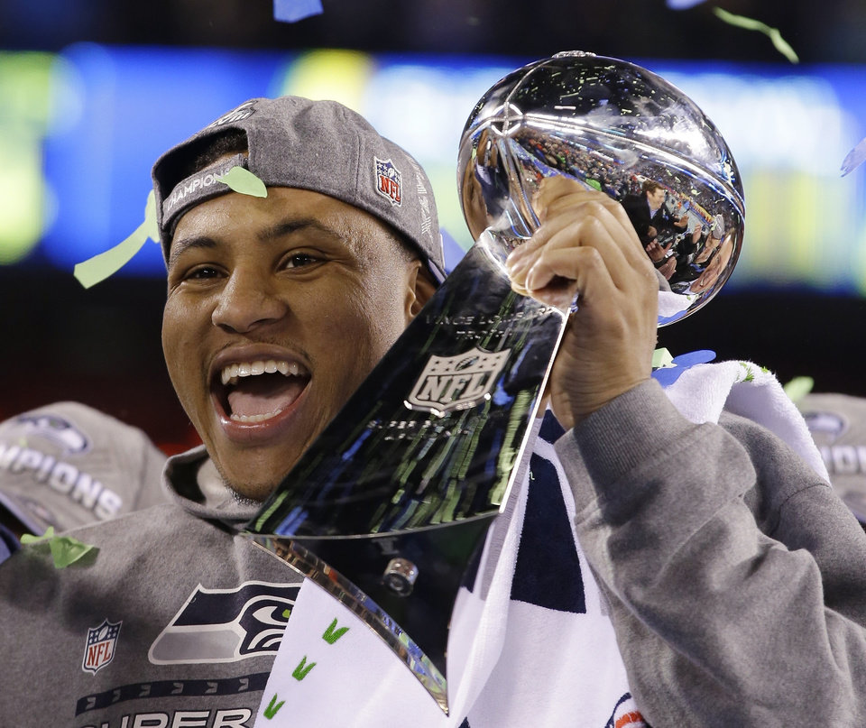 Photo - Seattle Seahawks' Malcolm Smith holds the Vince Lombardi Trophy after the NFL Super Bowl XLVIII football game against the Denver Broncos Sunday, Feb. 2, 2014, in East Rutherford, N.J. The Seahawks won 43-8. (AP Photo/Matt Slocum)