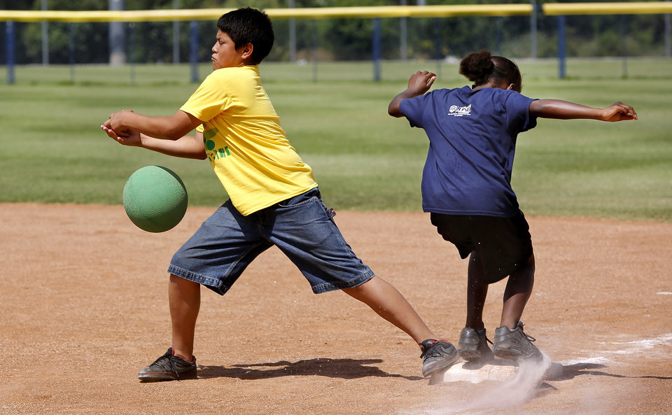 YOUTH KICKBALL TOURNAMENT / CHILD / CHILDREN / KIDS: First baseman Erlin Mejia, 12, with Southern Oaks Center team, has his foot planted on the bag, but is unable to grab the ball before the other team's runner makes it safely to first base. Kickball tournament at Hall of Fame Stadium Wednesday,  June 26, 2013.   Sponsored by the OKC Parks and Recreation Department and hosted by the Police Athletic League.  Photo  by Jim Beckel, The Oklahoman.