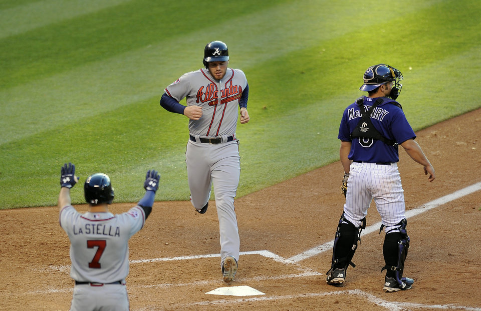 Photo - Atlanta Braves Tommy La Stella, left. congratulates Freddie Freeman, center, as he crosses home plate on an RBI single by Chris Johnson as Colorado Rockies catcher Michael McKenry, right, waits for the throw in the fourth inning of a baseball game on Monday, June 9, 2014, in Denver. (AP Photo/Chris Schneider)