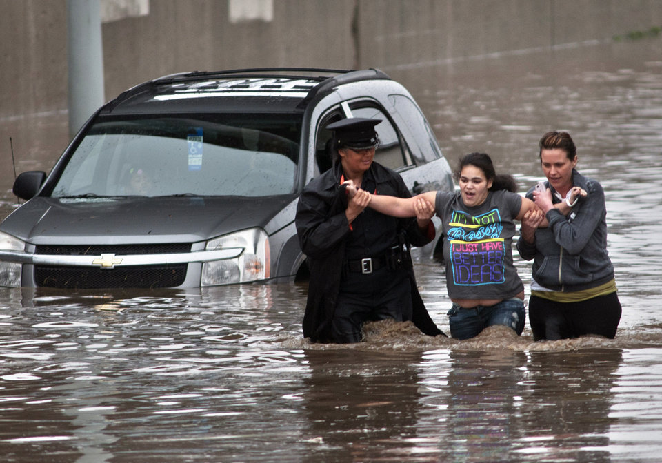 Photo - Police officer Shannon Vandenheuvel, left, and Melissa Kolenda, right, help Barbara Jones from her partially submerged car in Grand Rapids, Mich. Thursday, April 18, 2013. Middle America was getting everything nature has to throw at it on Thursday, from snow in the north to tornadoes in the Plains, and with torrential rains causing floods and transportation chaos in several states. (AP Photo/Grand Rapids Press, Chris Clark)